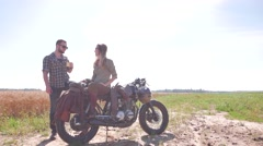 Happy couple on the vintage custom cafe racer resting in a field Stock Footage