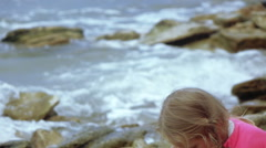 Child throwing stone into sea Stock Footage