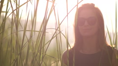 Young woman in a black dress and sunglasses straightens hair backlight at sunset Stock Footage