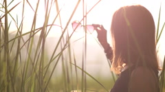 Young woman in a black dress puts on sunglasses sunset Stock Footage