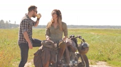 Cheerful couple on the vintage custom cafe racer resting in a field Stock Footage