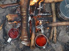 Campfire with tea and food in camping cookware Stock Photos