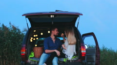 A young couple in the trunk decorated with twinkle lights. Stock Footage