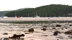 Sandy beach at ebb time with sea waves reflecting sunset light. Yachts in the Stock Footage