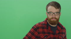 Young bearded man smiling and flirting, on a green screen background Stock Footage