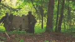 Soldiers moving a anti tank gun in a forest Stock Footage