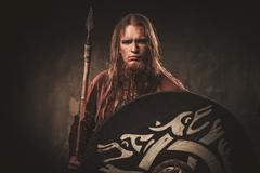 Serious viking with a spear in a traditional warrior clothes, posing on a dark Stock Photos