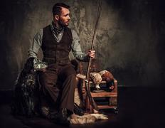 Handsome hunter with a english setter and shotgun in a traditional shooting Stock Photos