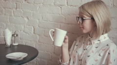 Happy young beautiful woman drinking coffe in the cafe and listening to music on Stock Footage