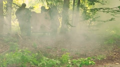 Soldiers moving a anti tank gun in a forest under a gas attack Stock Footage