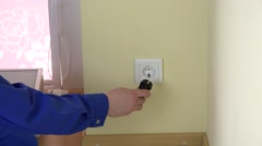 Man hand remove safety plug from outlet and insert plug wire Stock Footage