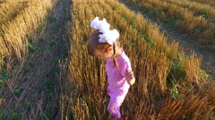 Girl child in sunglasses sneaks by cleaned field. Stock Footage