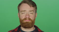 Young bearded man looking sad, on a green screen background Stock Footage