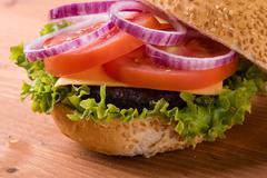 Homemade hamburger on wooden table Stock Photos