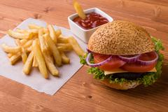 Homemade hamburger on wooden table with fries Stock Photos