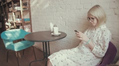 Happy young beautiful woman drinking coffe in the cafe and texting on her smart Stock Footage