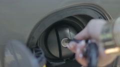 Female hand opening fuel filter cap with car key Stock Footage