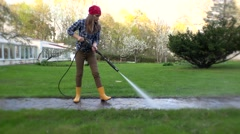 Housewife woman washing path in house yard Stock Footage
