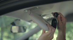 Closeup female hand taking car key from sun visor Stock Footage