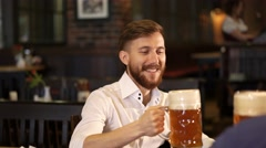 Young man drinking a beer in pub Stock Footage