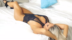 Sexy black lace lingerie girl on bed - playing with her long blond hair Stock Footage