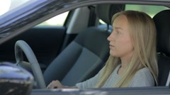 Charming young woman in car fastening seat belt Stock Footage