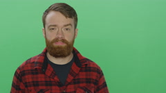 Bearded man shows discomfort, on a green screen background Stock Footage