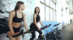 Two women talking while training in a spinning class in gym, 20s. 1080p Slow Stock Footage
