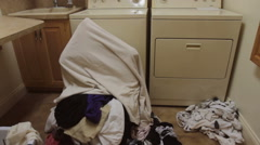Woman buried under pile of dirty laundry in laundry room of home. Stock Footage