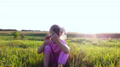 Little girl with enthusiasm plays on the smartphone. Stock Footage