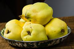 Yellow quince on wooden table Stock Photos