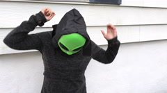 Person dressed in black dancing in a green alien mask Stock Footage