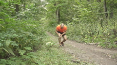 Young Man Having a Cramp While Jogging. Stop And To Massage the Knee. Man Run Stock Footage