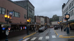 Street lights come on as evening comes to rainy front street Juneau AK. Stock Footage