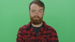 Bearded man smiles and makes silly faces, on a green screen background Stock Footage
