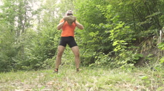 Man In Summer Forest Lifts A Heavy Stone. Stock Footage