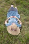 Free woman enjoying freedom feeling happy while lying on grass with hat on fa Stock Photos