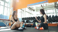 Women sitting on exercise mats and socializing while on break at the gym 20s Stock Footage