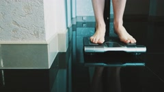 Girl walk on floor stand up on modern scales in apartment. Weighing. Slimness Stock Footage