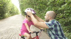 Father dresses helmet on daughters head before she starts to ride her bike. H Stock Footage