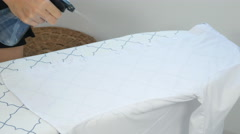 Closeup of woman ironing clothes on ironing board Stock Footage