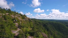 Aerial high shot of a family above tall cliff and mountain forest Stock Footage