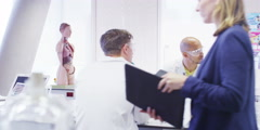 Female teacher teaching group of university students in a science class Arkistovideo
