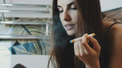 Young girl sitting in bathroom with smartphone. Smoking electronic cigarette Stock Footage