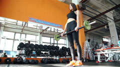 Young woman doing exercises on training apparatus in gym 20s. 1080p Slow Motion Stock Footage
