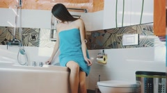 Young girl in blue towel walk into bathroom opening water faucet. Taking bath Stock Footage