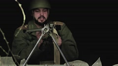 A solder is trying to reload a broken machine gun Stock Footage