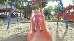 Little girl riding a roller coaster at the playground  smiles for the camera. Stock Footage