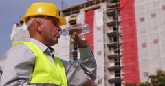 Thirsted Engineer Drinking Water in Front of Construction Site New Building Stock Footage