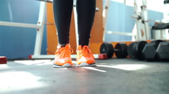 A woman in sport orange outfit jumps the rope inside in the gym 20s. 1080p Slow Stock Footage